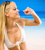 Young beautiful smiling woman in white bikini on beach — Stock Photo
