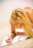 Young beautiful woman in bikini writing on sea beach — Stock Photo