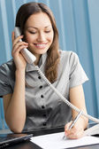 Successful businesswoman with phone at office — Stock Photo