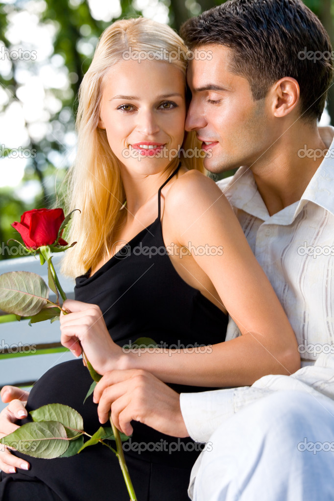 Happy pregnant woman with rose and her husband, outdoors  Stock Photo #6305054