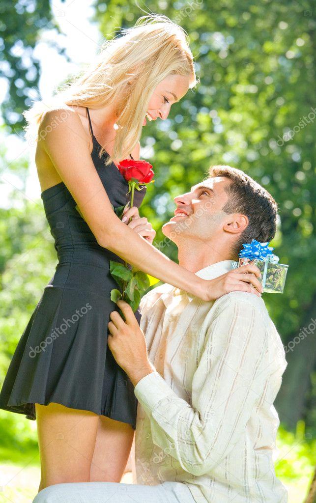 Heureux dr le jeune couple avec cadeau et de rose de plein air photographi - Cadeau pour jeune couple ...