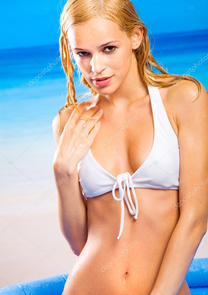 Young beautiful tanned blond wet woman in bikini on beach
