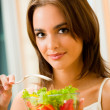 Young happy smiling woman with salad at home — Stock Photo