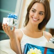 Stock Photo: Young happy smiling woman with gift boxes at home