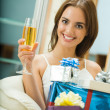 Young happy smiling woman with gifts and champagne at home — Stock Photo #6312141