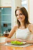 Young woman with glass of redwine and salad at home — Stock Photo