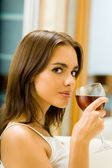 Young woman with glass of red wine, indoors — Stock Photo