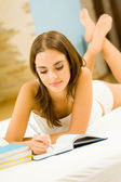 Young woman with notebook or organiser at home — Stock Photo