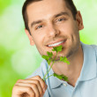 Young attractive happy smiling man with potherbs, outdoors — Stock Photo #6325043