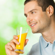 Portrait of young happy smiling man drinking orange juice, outdo — Stock Photo
