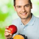 Portrait de jeune homme souriant heureux avec assiette de fruits, outdoo — Photo