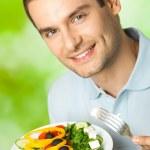 retrato de jovem feliz comendo salada de, ao ar livre — Foto Stock
