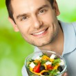 Portrait of young happy smiling man with plate of salad, outdoor — Stok fotoğraf