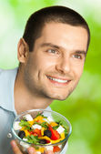 Portrait of young happy man eating salad, outdoors — Stock Photo