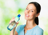 Young smiling woman with bottle of water, outdoors — Stock Photo