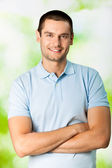 Portrait of young attractive smiling man, outdoors — Stock Photo