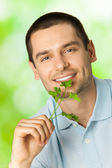 Young attractive happy smiling man with potherbs, outdoors — Stock Photo