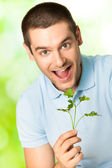 Young happy smiling man with potherbs, outdoors — Stock Photo