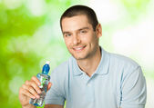 Young happy smiling man with bottle of water, outdoors — Stock Photo