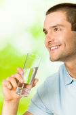 Young smiling man with glass of water, outdoors — Stock Photo
