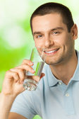 Young happy smiling man drinking water, outdoors — Stock Photo