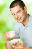 Portrait of young happy smiling man drinking coffee, outdoors — Stock Photo