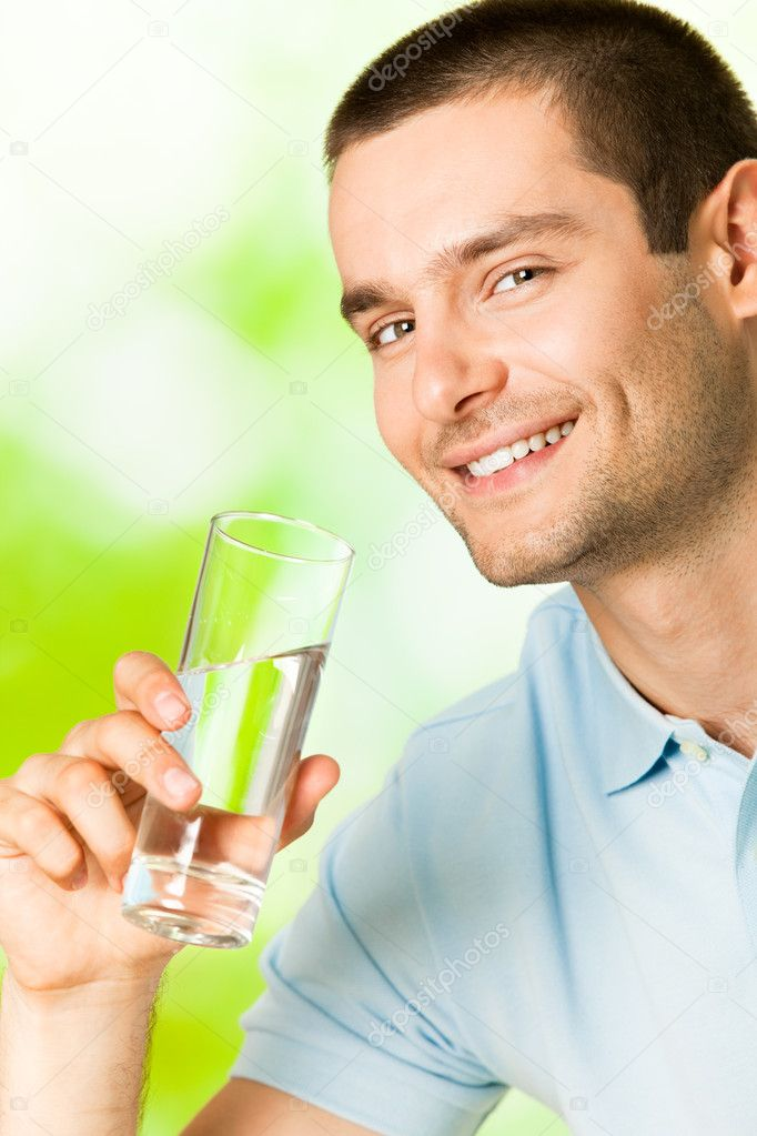 Young smiling man with glass of water, outdoors — Stock Photo #6325178
