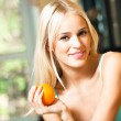 Portrait of young happy smiling woman with orange at home — Stock Photo #6395899
