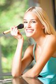 Portrait of smiling beautiful young woman with makeup brush indo — Stock Photo