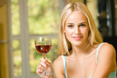 Portrait of young beautiful woman with red-wine glass, indoors — Stock Photo
