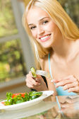 Young happy smiling woman eating salad at home — Stock Photo