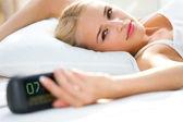 闹钟早上在床上的年轻女人 — 图库照片