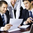 Three businesspeople working with document at office — Stockfoto