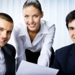Three businesspeople working with document at office - Stock Photo