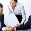 Three businesspeople handshaking with document at office — Stock Photo
