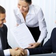 Stock Photo: Three businesspeople handshaking with document at office