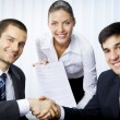Three businesspeople handshaking with document at office — Stockfoto #6429186