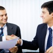 Two businesspeople, or businessman and client, with document han — Stock Photo