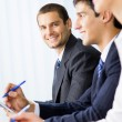 Three happy smiling businesspeople at meeting, presentation or c — ストック写真