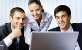 Three businesspeople working with laptop at office — Stok fotoğraf