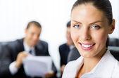 Porträtt av framgångsrik affärskvinna och kollegor på bak — Stockfoto