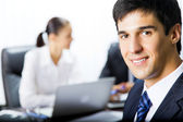 Businessman and colleagues on background, at office — Stock Photo