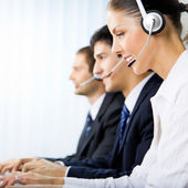 Three support phone operators at workplace — ストック写真