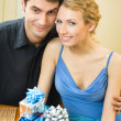 Young couple celebrating with champagne and gifts at home — Stock Photo #6477007