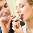 Young amorous couple eating cookies together at home — Stock Photo