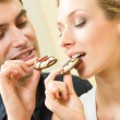 Stock Photo: Young amorous couple eating cookies together at home