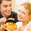 Young happy couple eating salad at home together — Stock Photo
