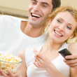 Young couple eating popcorn and watching TV together at home — Stock Photo
