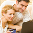 Young happy couple paying by credit card in internet shop — Stock Photo