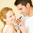Young couple cleaning teeth together at bathroom — Stock Photo